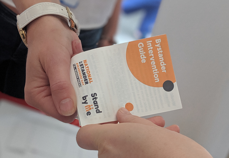 Picture of people passing Communities Inc's Bystander Intervention Guide to one another.